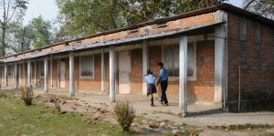 Two young students walk outside one of the classrooms at Moran Memorial School in Nepal. Source: D.Lee/Eyrie Foundation.